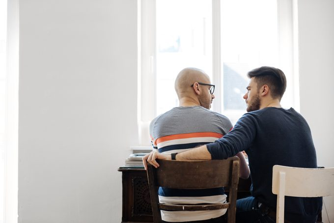 Back Shot Of Gay Couple Sitting Together