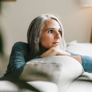 Pensive woman on the couch at home
