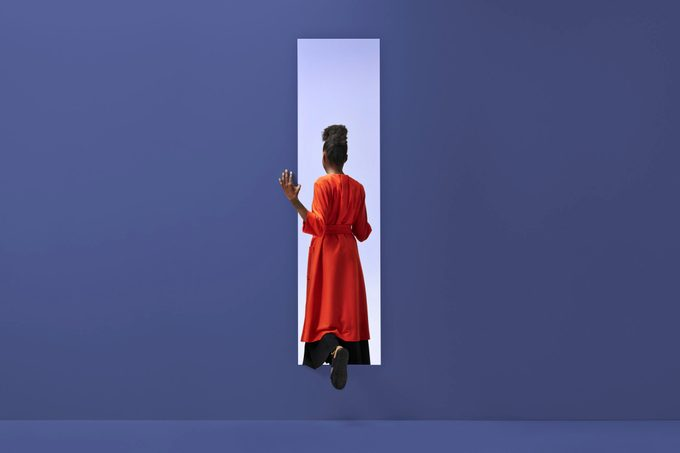 Woman walking into rectangular opening in colored wall