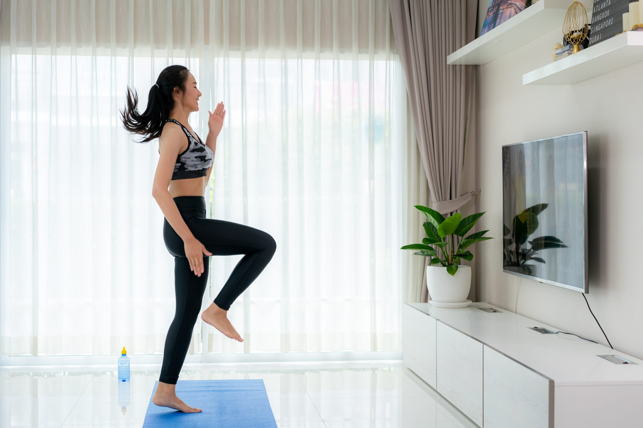 "Asian woman doing strength training cardio aerobic dance exercises ""u201cHigh Knee""u201d while watching videos fitness workout class live streaming online on a smart tv in the living room at home."