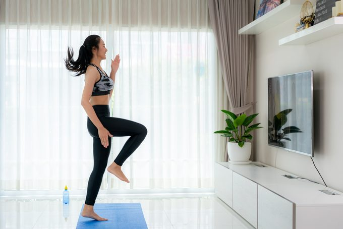 """Asian woman doing strength training cardio aerobic dance exercises """"u201cHigh Knee""""u201d while watching videos fitness workout class live streaming online on a smart tv in the living room at home."""