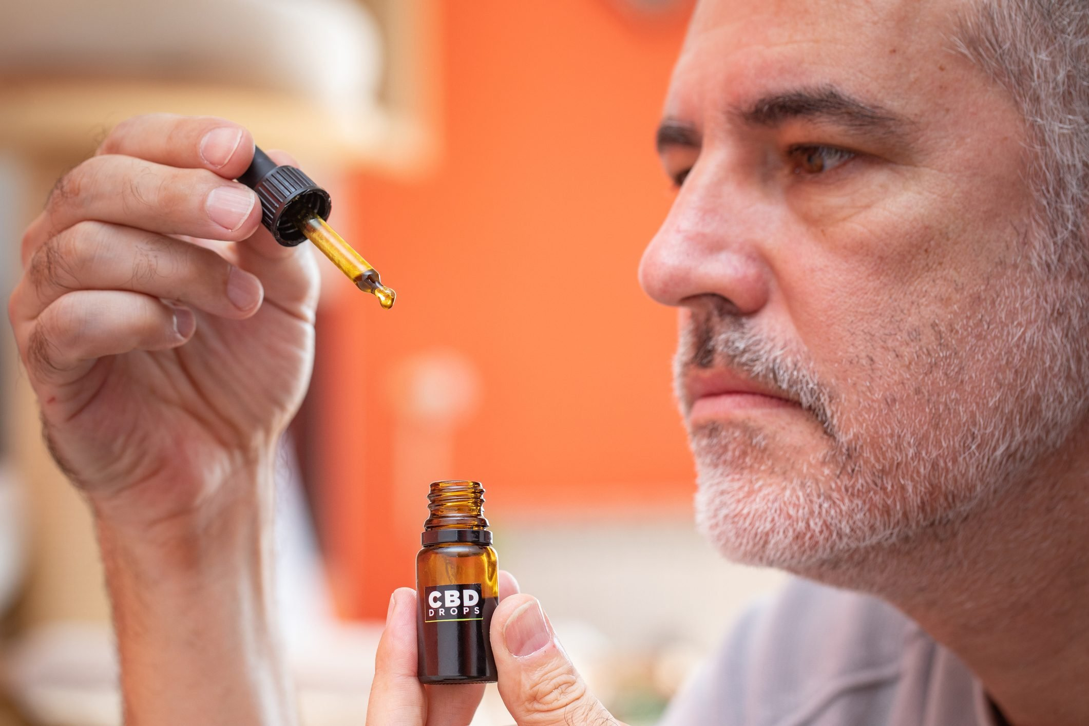 Mature Man Using CBD Oil at Home - Stock Photo