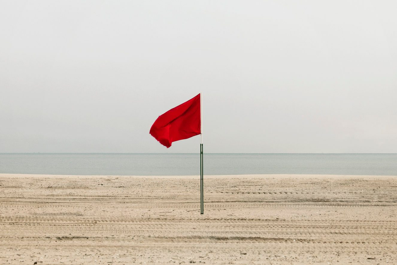 Red flag on empty beach, Coney Island, Brooklyn, New York
