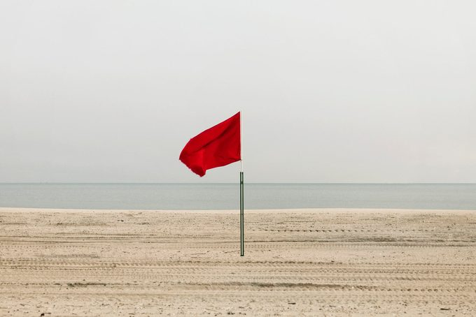 Red flag on empty beach, Coney Island, Brooklyn, New York