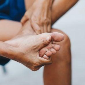 Hand Touching Feet In Pain
