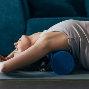 Working Out at Home Woman is Sportswear Using a Roller to Massage Back Muscles