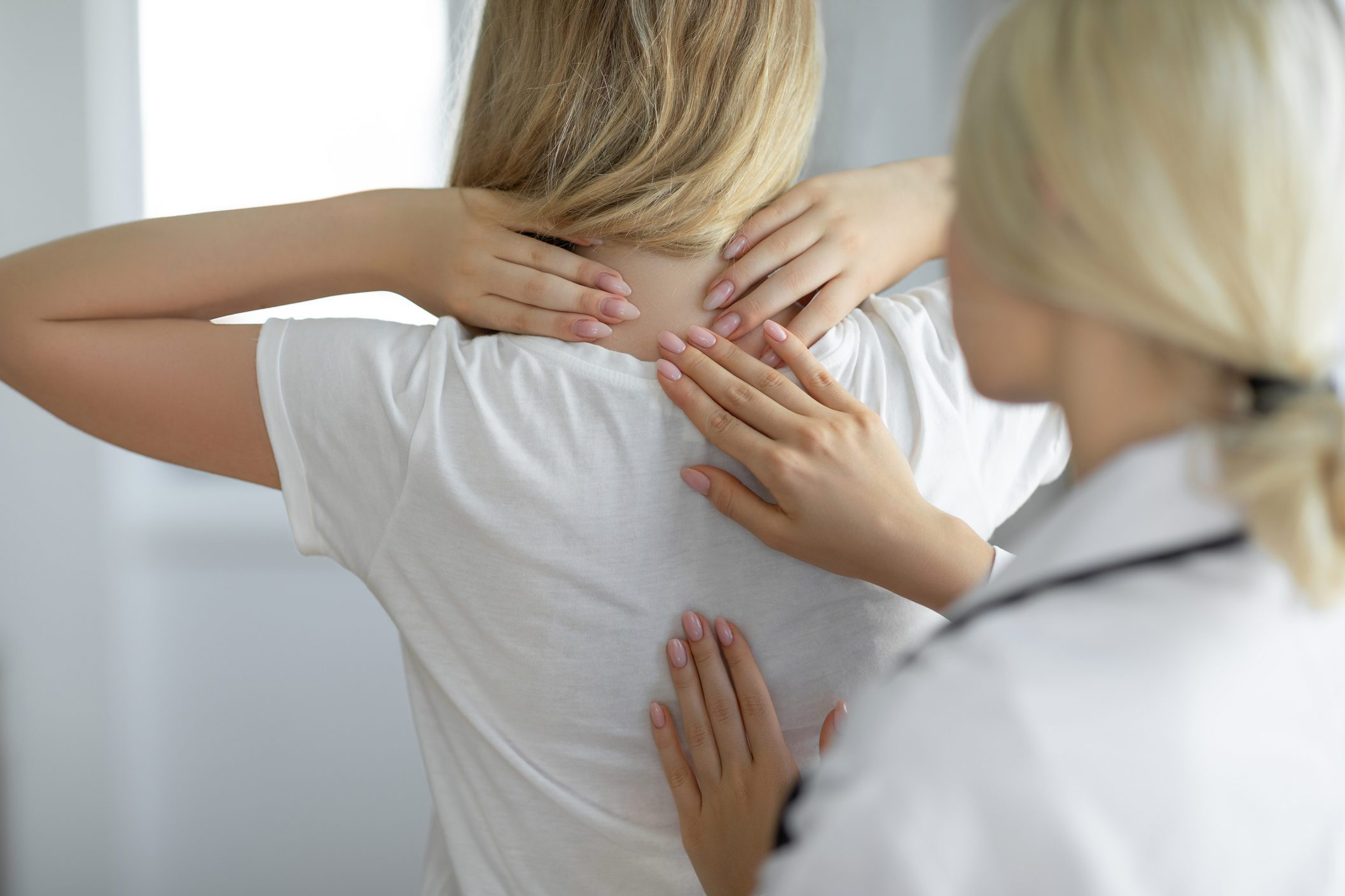 Female doctor is examining her neck