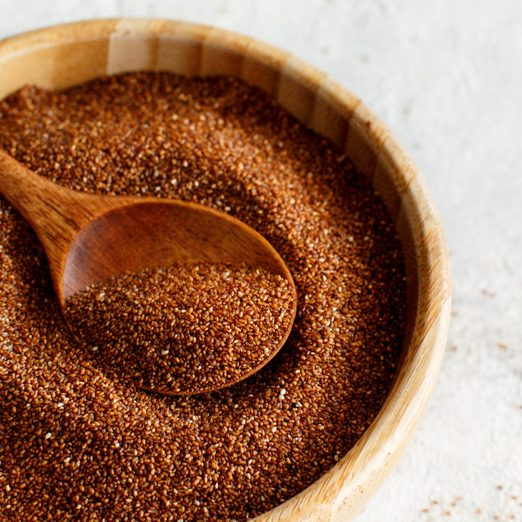 Uncooked teff grain with a wooden spoon close up