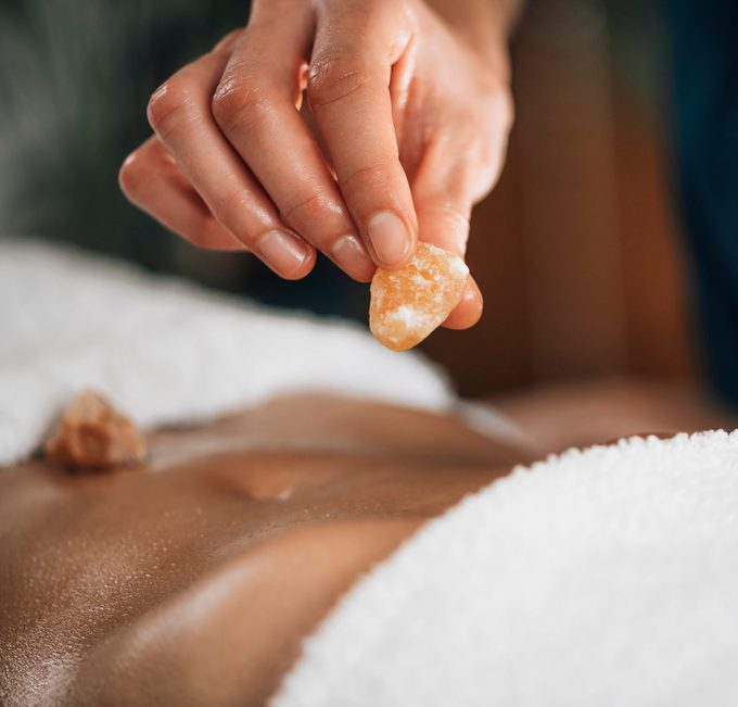 Ayurvedic Practitioner Using Gemstones And Crystals For Healing Female Patient Chakras