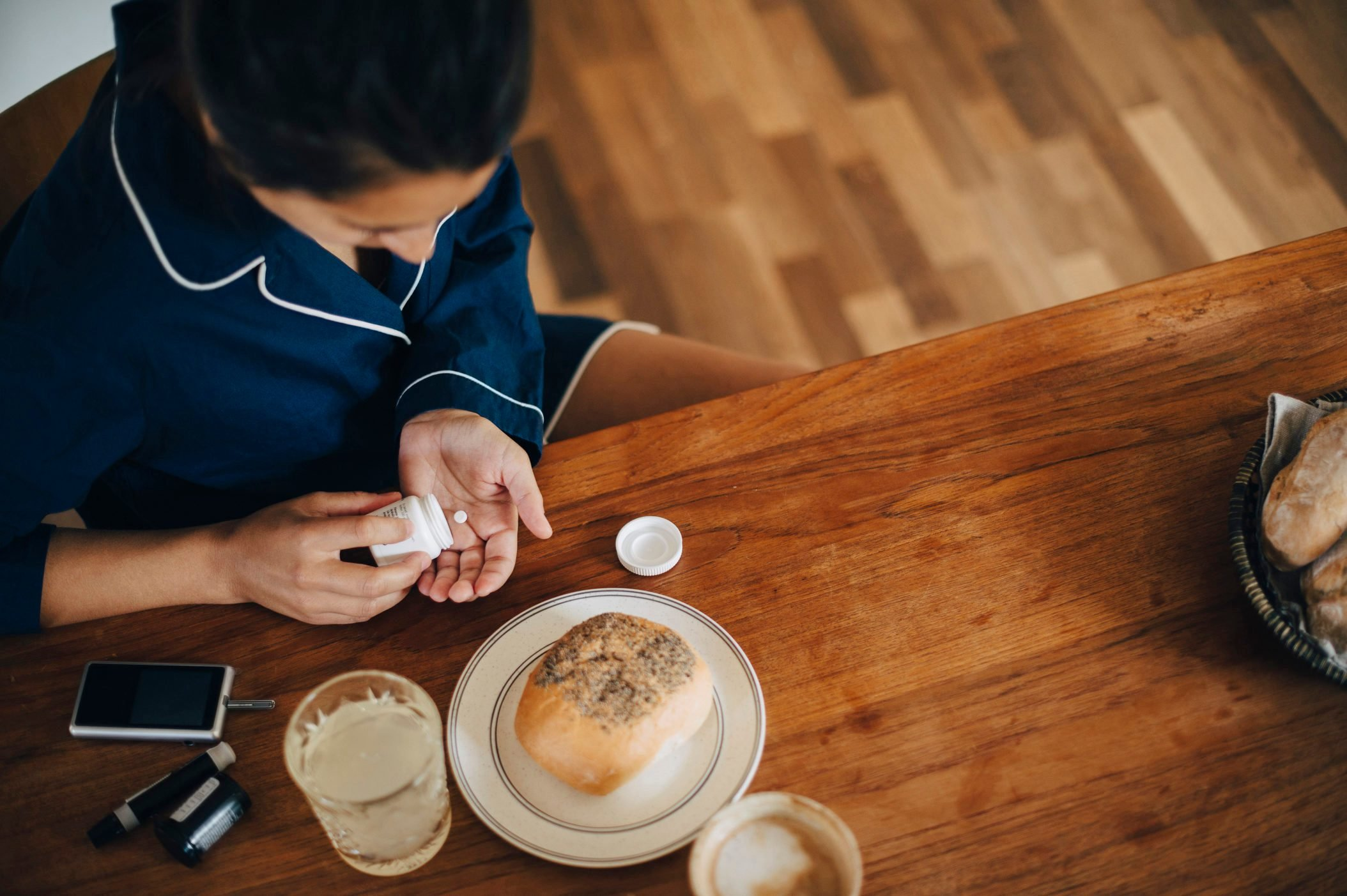 High angle view of woman taking medicine while having breakfast at table