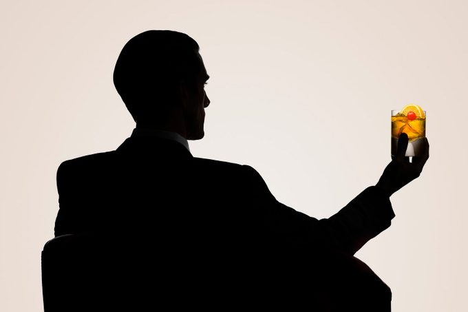 Silhouetted male sitting in a chair with whisky
