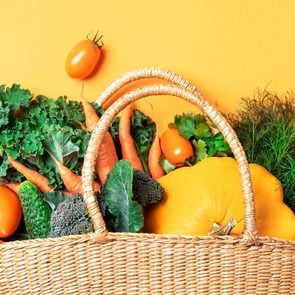 Straw basket with organic vegetables over trendy yellow background. Healthy food, vegetarian diet. Eco friendly, zero waste, plastic free concept.