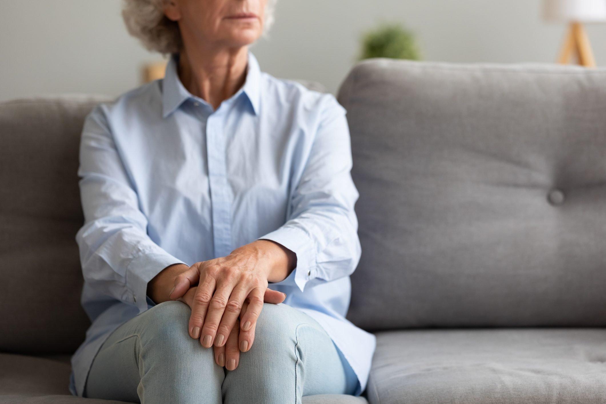Unhappy depressed senior woman sit alone on sofa, closeup view