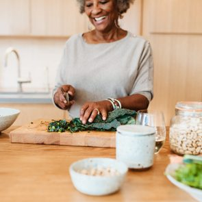 Senior female chopping vegetable at kitchen island