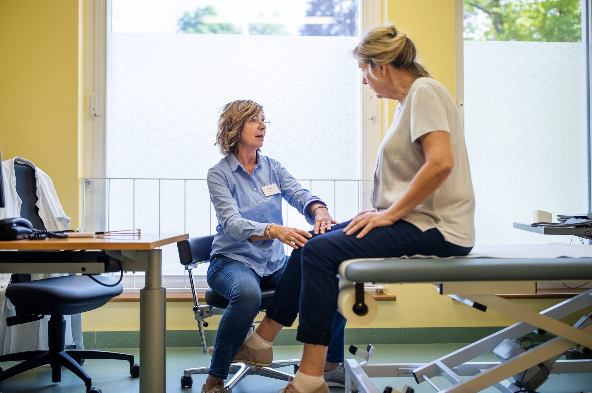 Physiotherapist checking knee of female patient stock