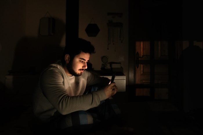 Young man in bed looking at his smartphone screen