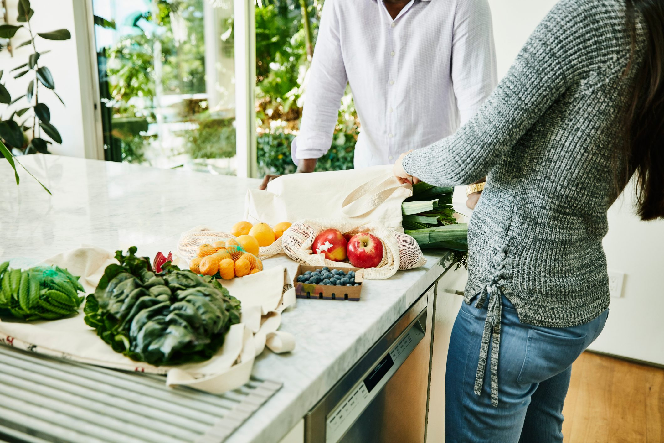 Couple organizing fresh organic vegetable and fruit on kitchen counter after shopping