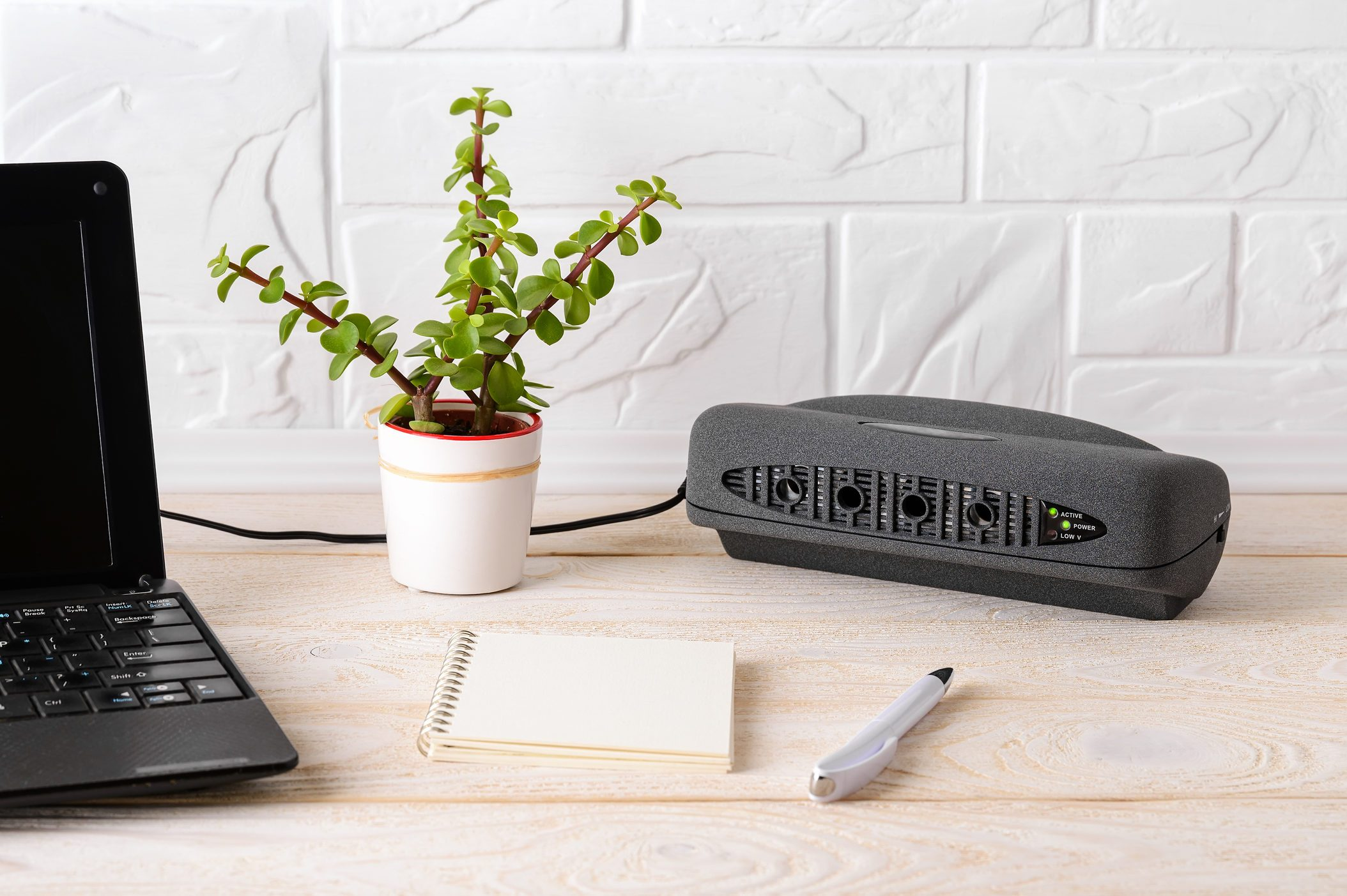 Black air ionizer near laptop on a white wooden table