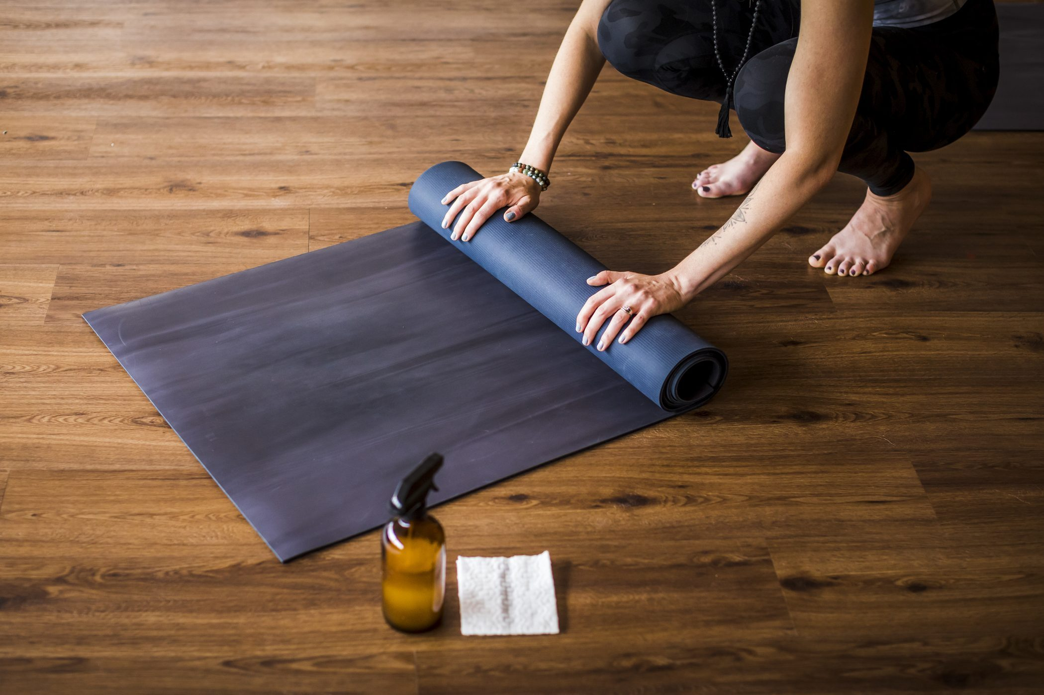 Woman rolling up yoga mat with sanitizer nearby.
