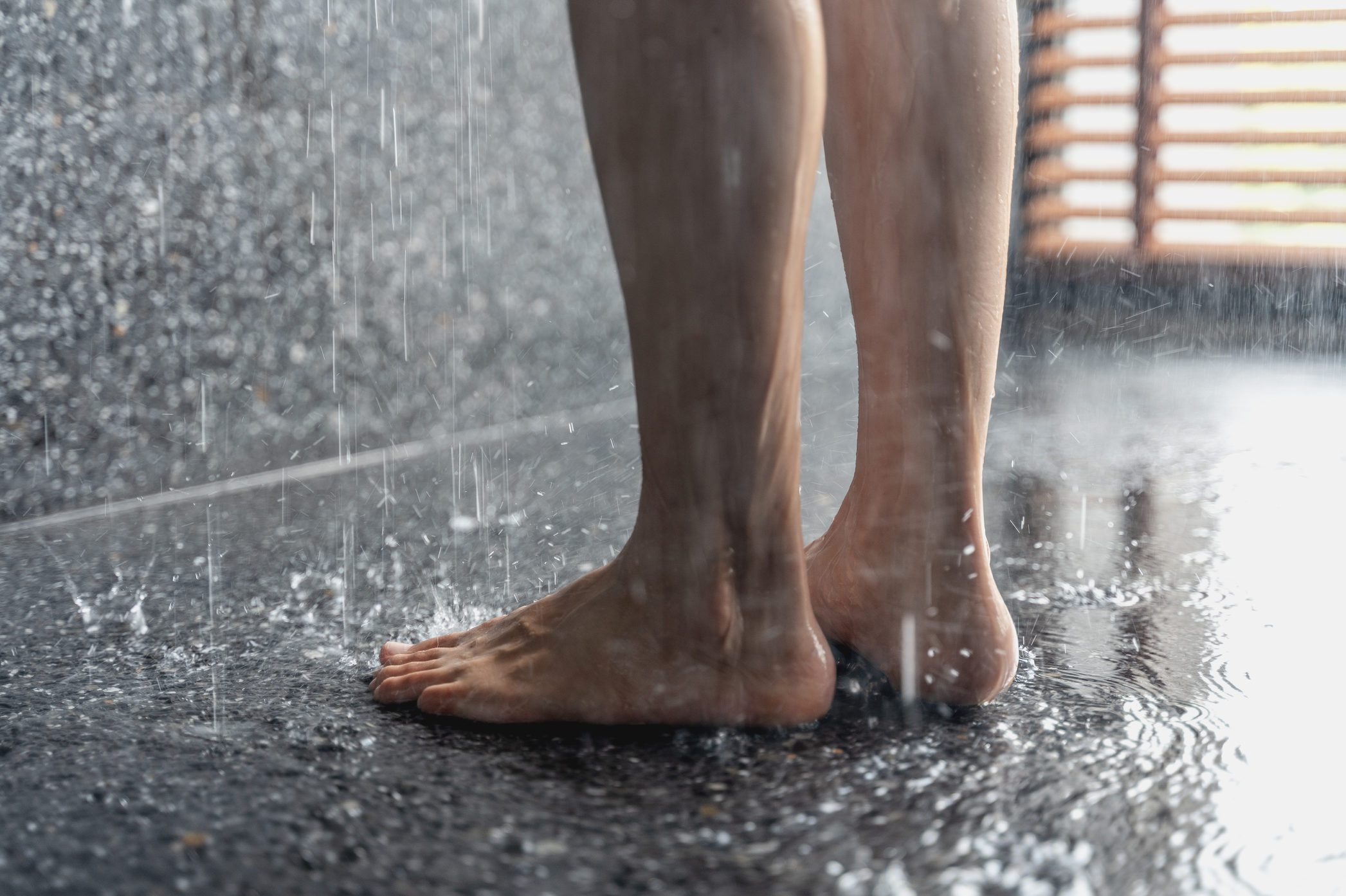 Legs and feet of someone standing in shower
