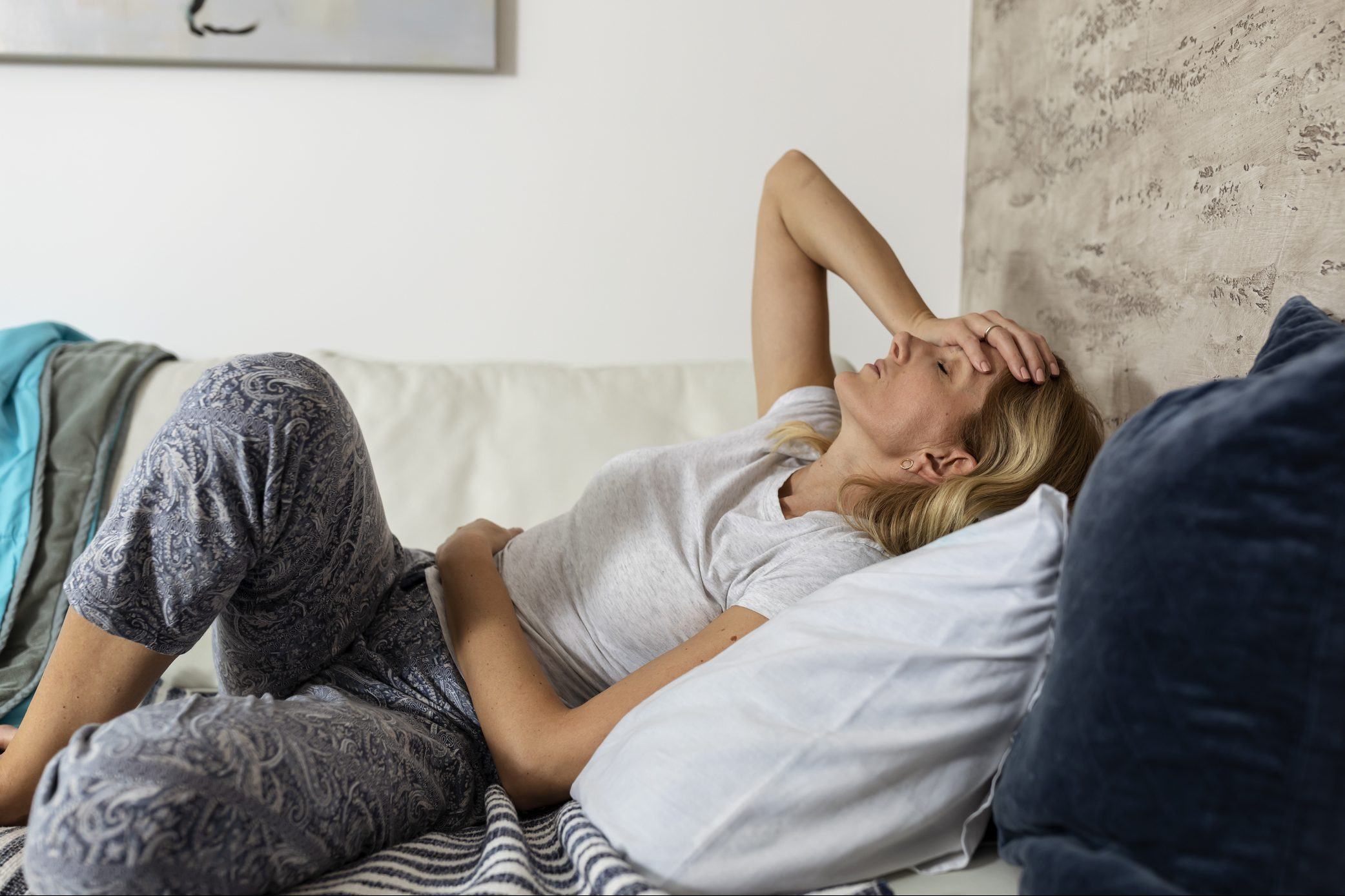 Mature woman lying on the bed suffering from stomachache and painful period cramps