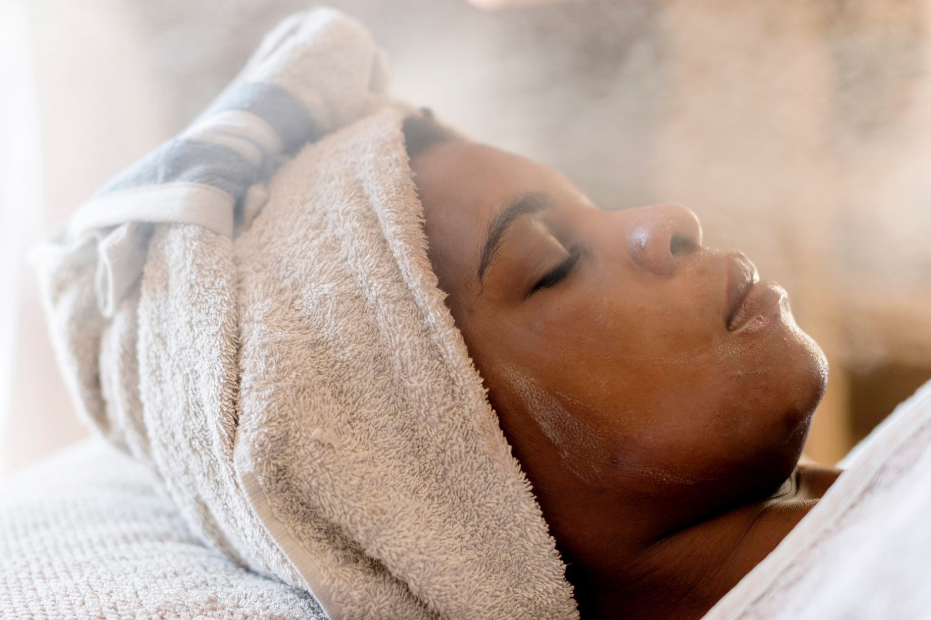 woman with towel on her hair receiving steam treatment at spa
