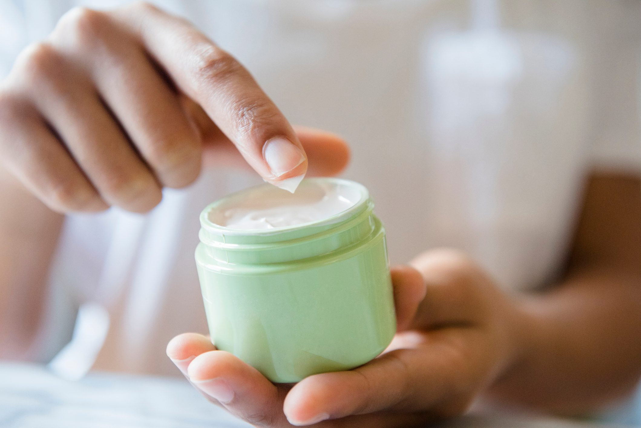 Close up of African American woman dipping finger in lotion jar