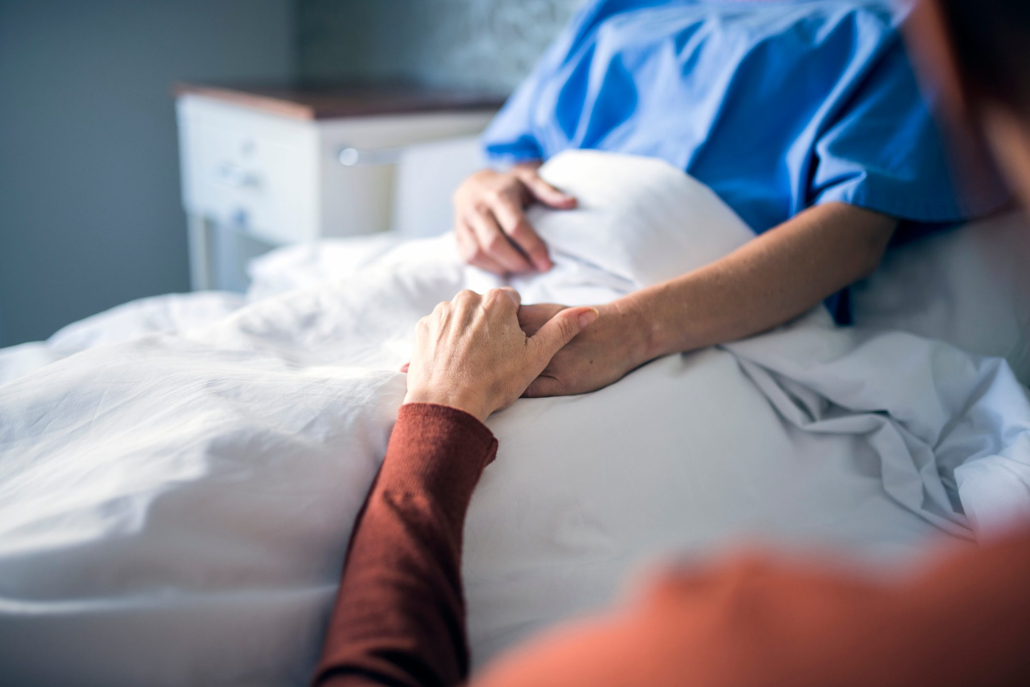 Woman holding hand of sister in hospital bed