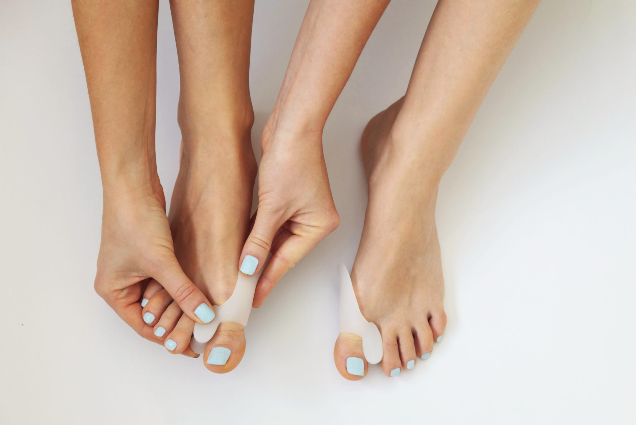close up of woman putting bunion corrector on feet