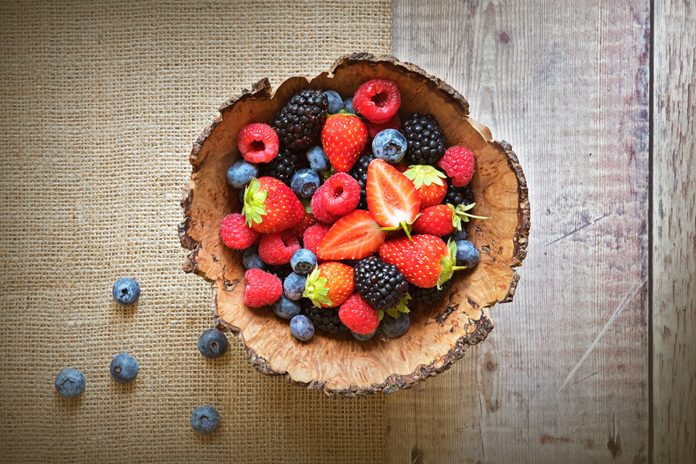 Close-up image of a wooden bowl full of Healthy Summer berries including Strawberries, raspberries, black berries and blue berries