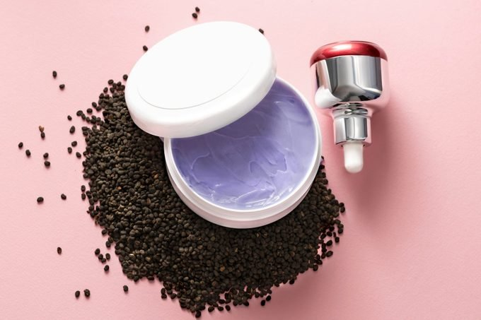 Babchi dry raw seeds (Psoralea Corylifolia) on pink surface with various kinds of cosmetic products. Bakuchiol cosmetics concept.