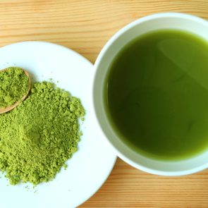 Top View of a Cup of Hot Matcha Green Tea with a Plate of Matcha Tea Powder on Wooden Table