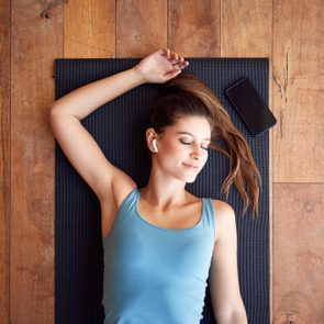 Overhead View Of Woman Lying On Exercise Mat Wearing Wireless Earphones Connected To Mobile Phone