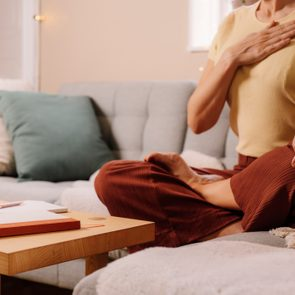 Woman indoors relaxing meditating and doing breathing exercises