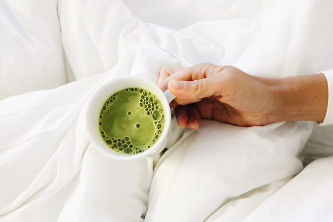 High Angle View Of Woman Holding Matcha Latte In A Mug In Bed