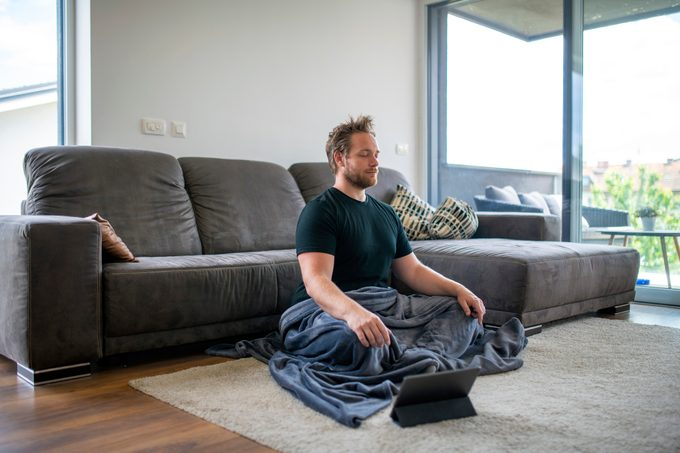 Caucasian Man Meditating Using Digital Tablet in the Living Room
