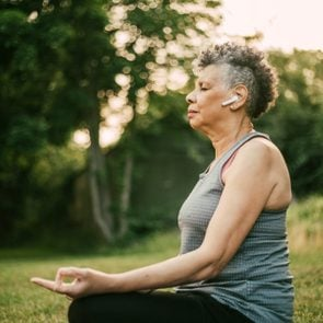 Side view of senior woman with in-ear headphones sitting in lotus position at park