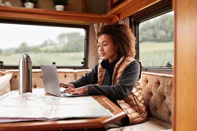 Woman using laptop in camper van