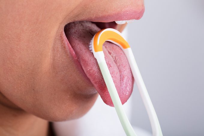 Woman Cleaning Tongue