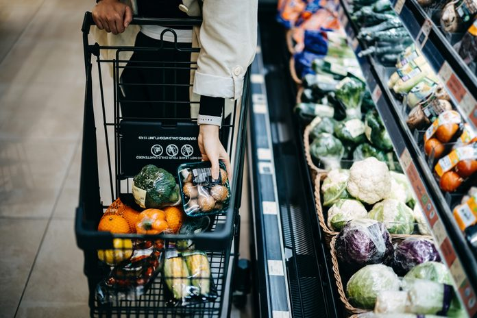 Close up of woman's hand shopping for fresh groceries in supermarket and putting a variety of organic vegetables in shopping cart