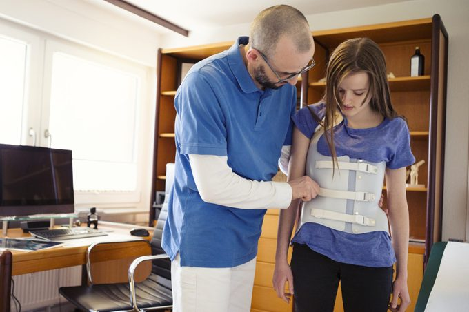 Male GP in a German medical office, assessing teenage girl wearing back brace for Scoliosis correction