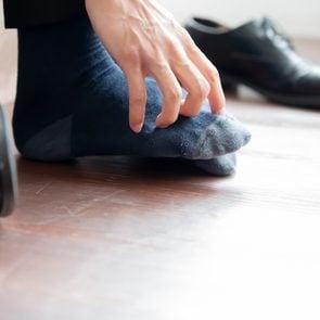 man itching his foot close up