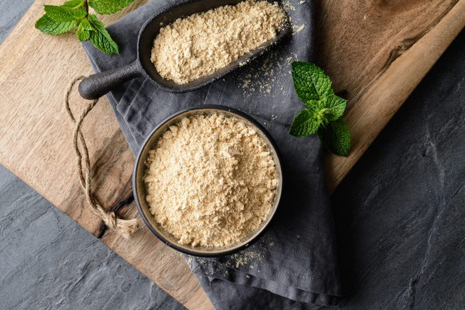 Dietary supplement, Maca root powder in a bowl and scoop with copy space