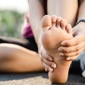Low Section Of Woman Touching Foot In Pain While Sitting On Road