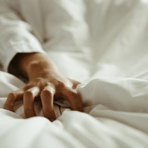 Close up hand of female pulling white sheets in ecstasy , feeling and emotion concept