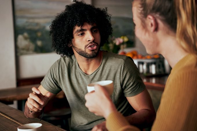 Young African American man with an afro in serious conversation with woman while sitting in a cafe and drinking coffee - two diverse friends chatting in a coffee shop