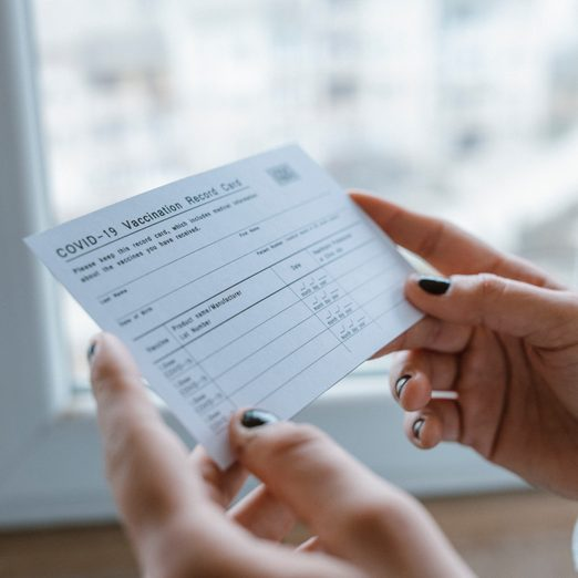 Woman holding COVID-19 Vaccination Record Card.