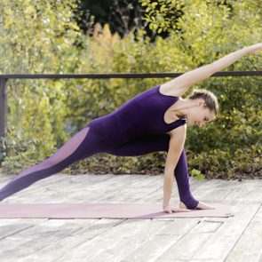 Woman practicing yoga on wooden deck against trees