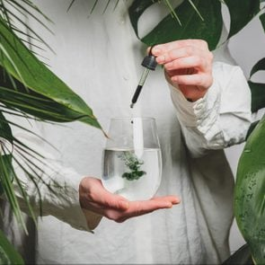 woman in a white shirt adds drops of chlorophyll to glass of water standing next to palm trees