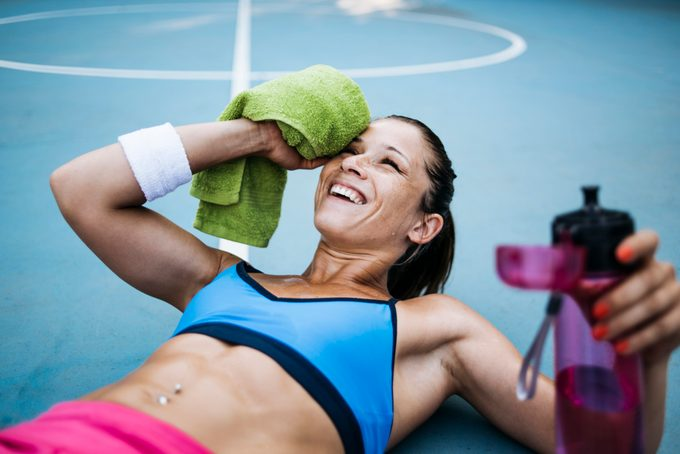 A woman wipes the sweat off her face